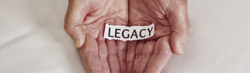 Cropped shot of a person holding a piece of paper with the word legacy written on it